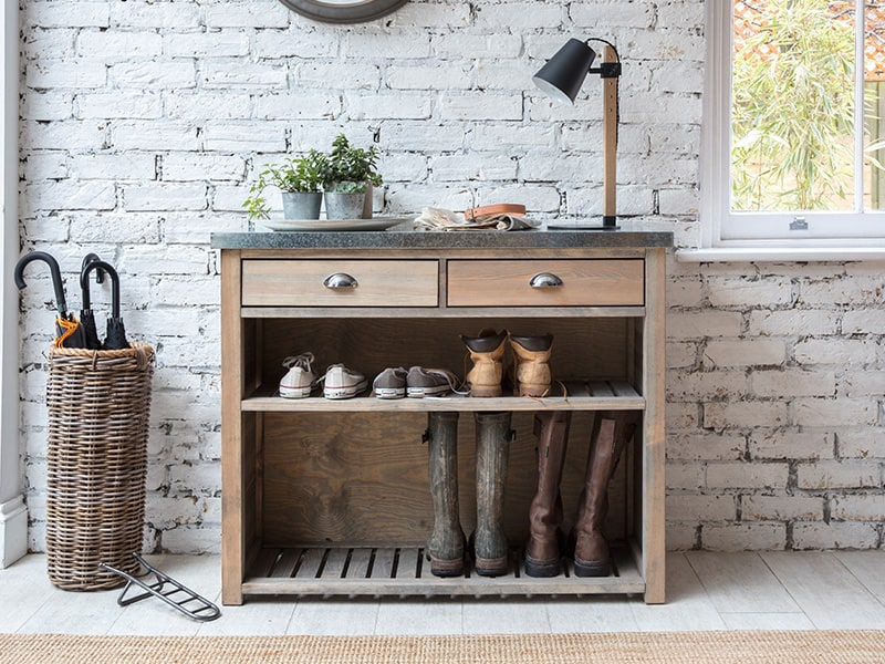 Wicker umbrella stand, wooden storage unit containing shoes and laid with plants and lamp. All set against a white painted brick wall.