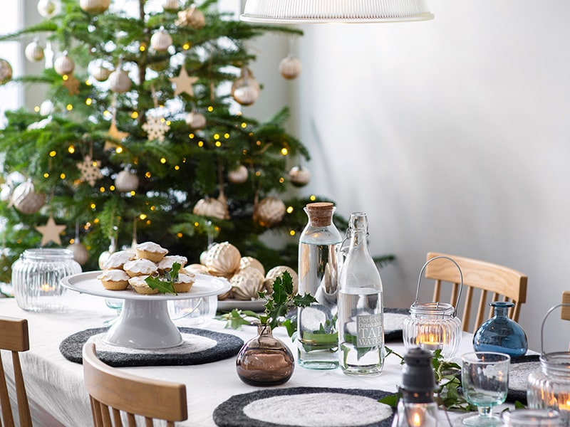 Table laid with candles, vases and mince pies