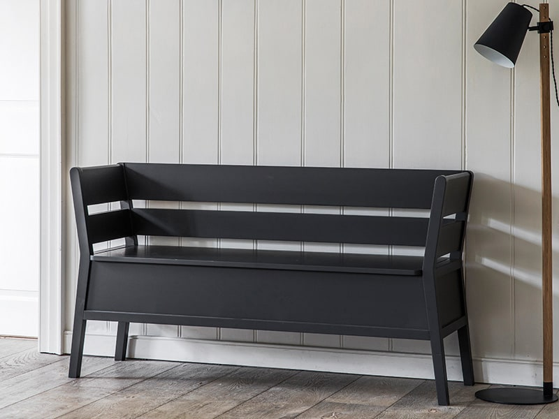 Storage bench set against cladded cream wall in a hallway, next to a floor lamp
