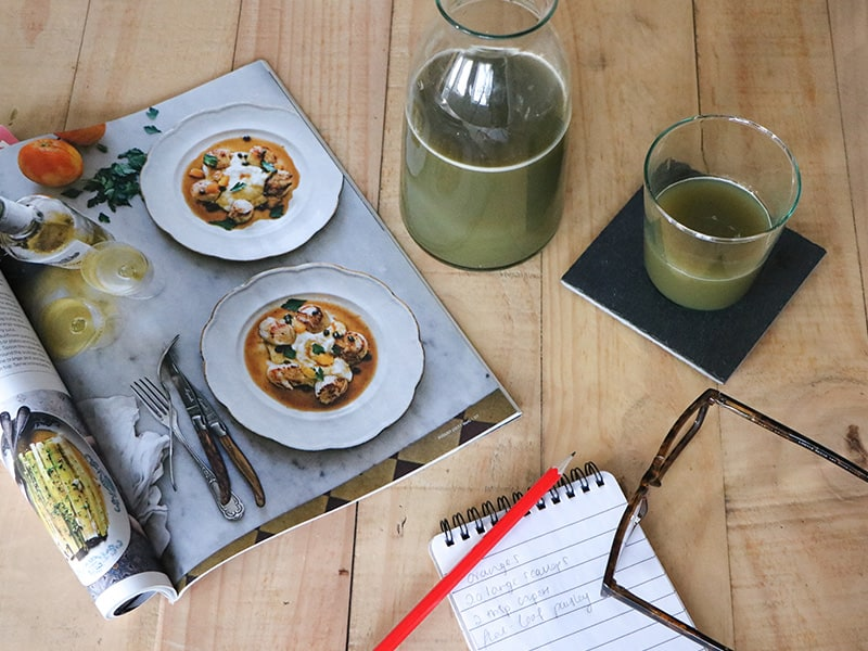 Green smoothies with a healthy recipe and shopping list on a table