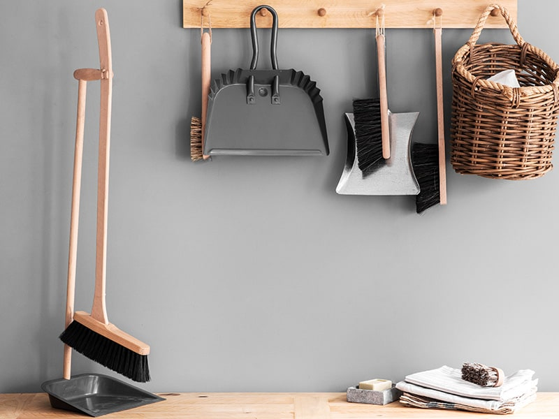 Selection of dustban and brushes hanging from a wal shelf
