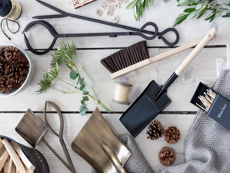 Mutiple accessories, foliage, fir cones and fireside tools on a wooden table