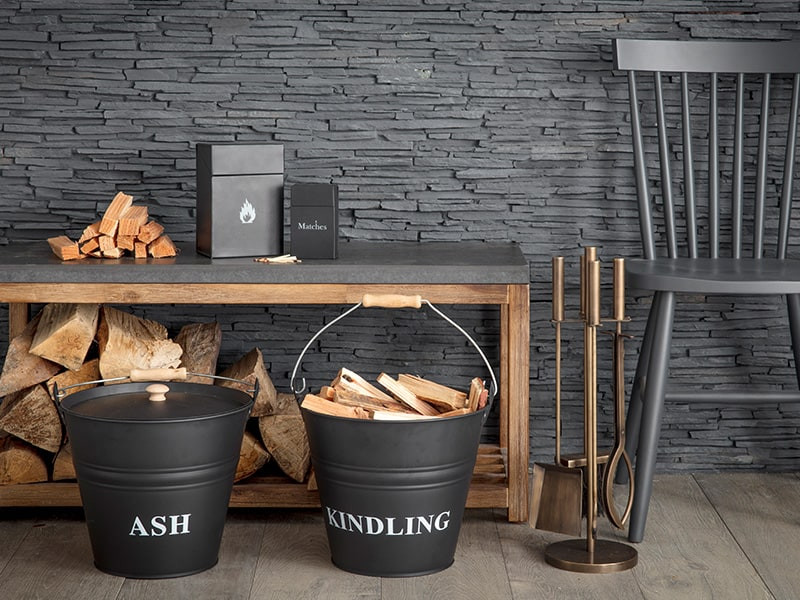 Carbon coloured fireside accessories with wood and kindling. Set against a textured slate wall