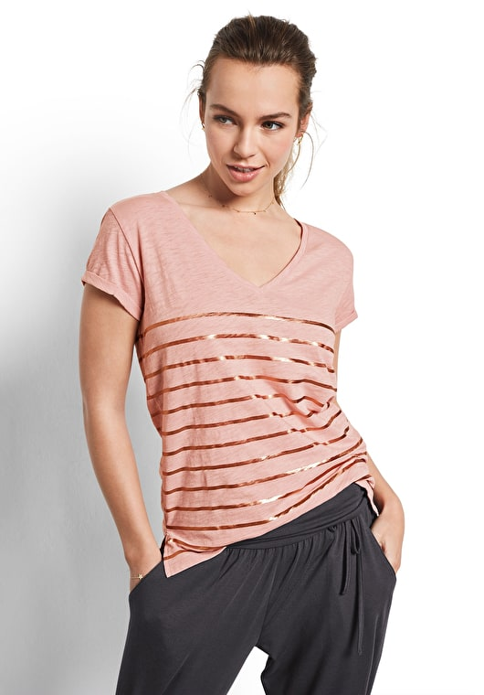 Model wears our V neck striped tee with rolled capped sleeves in blush and metallic gold stripes