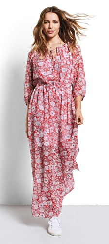 Model wears lightweight flowing coral maxi dress with a stunning hibiscus print sinched in at the waist