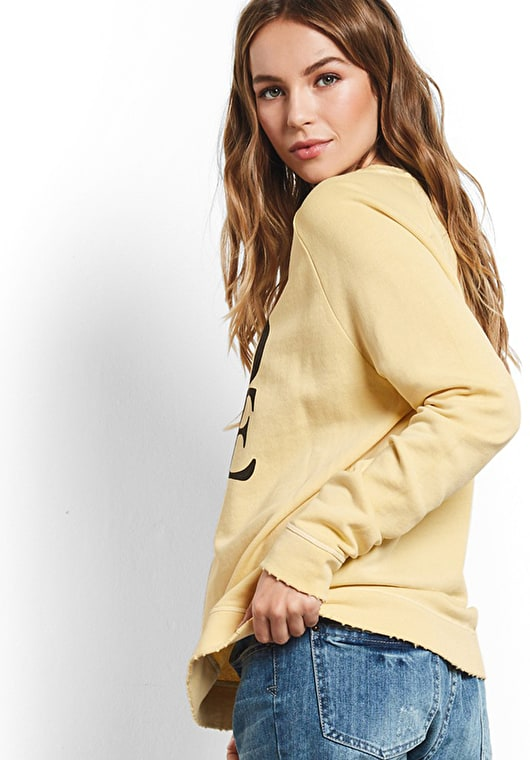 Model wears our Long sleeve sweat top with 60s inspired love motif in washed yellow and asphalt