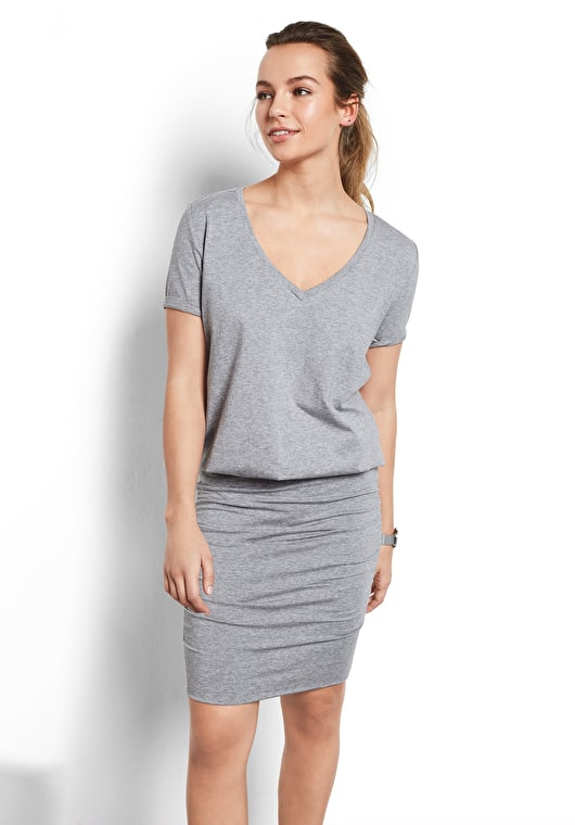Model wears our Tara dress is made up of a tight skirt and a v neck tee, in a beautiful grey marl.