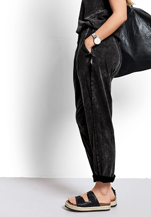 Model wears our lightweight jumpsuit with a tie waist in a washed out black
