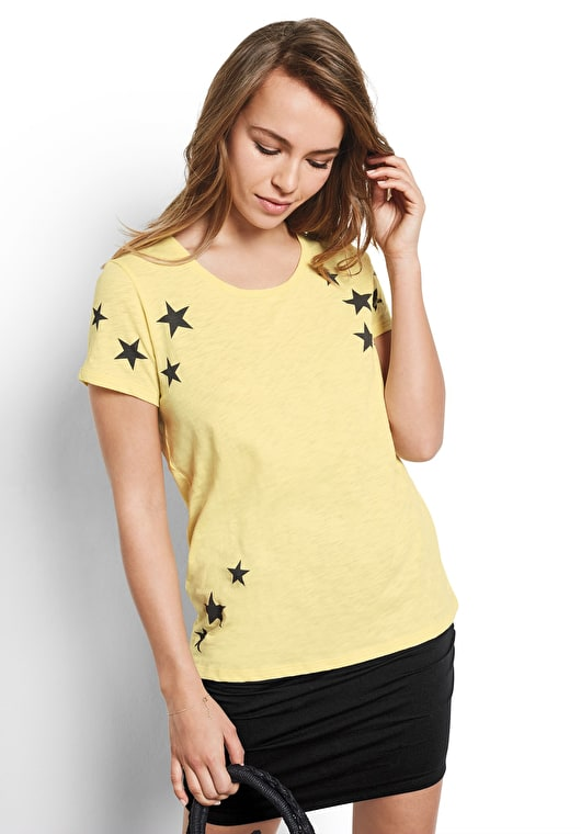 Model wears our Scatter Star printed crew neck tee in pastel yellow with asphalt stars