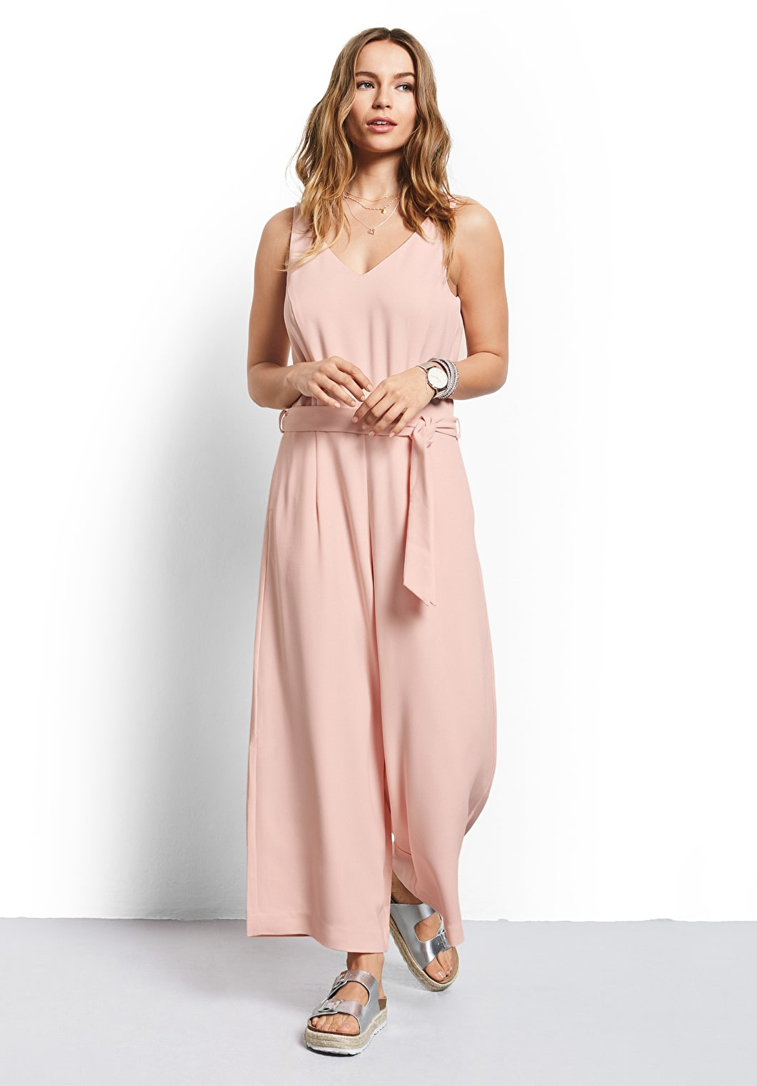 Model wears our jumpsuit with a detachable belt, wide leg trousers and a v neckline in blush