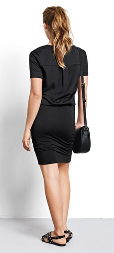 Model wears our Tara dress is made up of a tight skirt and a v neck tee, in a classic black.