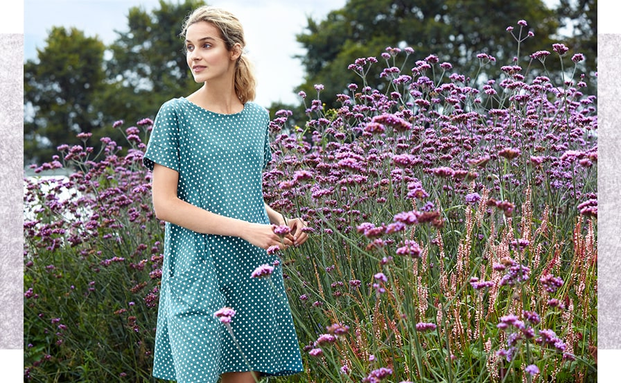 Kestle Barton Garden dress in green with white polka dots being worn by blonde girl next to purpler flowers