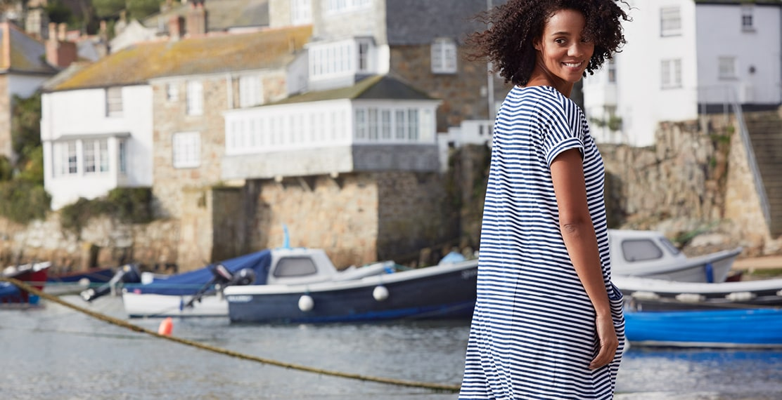 Girl looking back at the camera wearing a breton striped dress in Mousehole Harbour.
