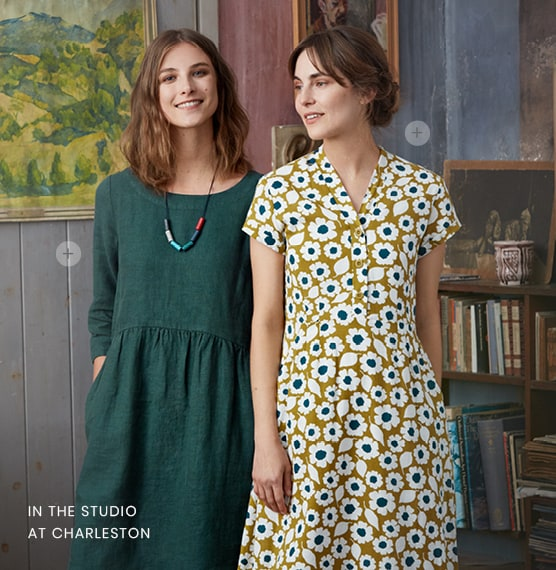 2 Ladies posing in Studio of Charleston House, one wearing a dark green dress & the other wearing a yellow flowery dress