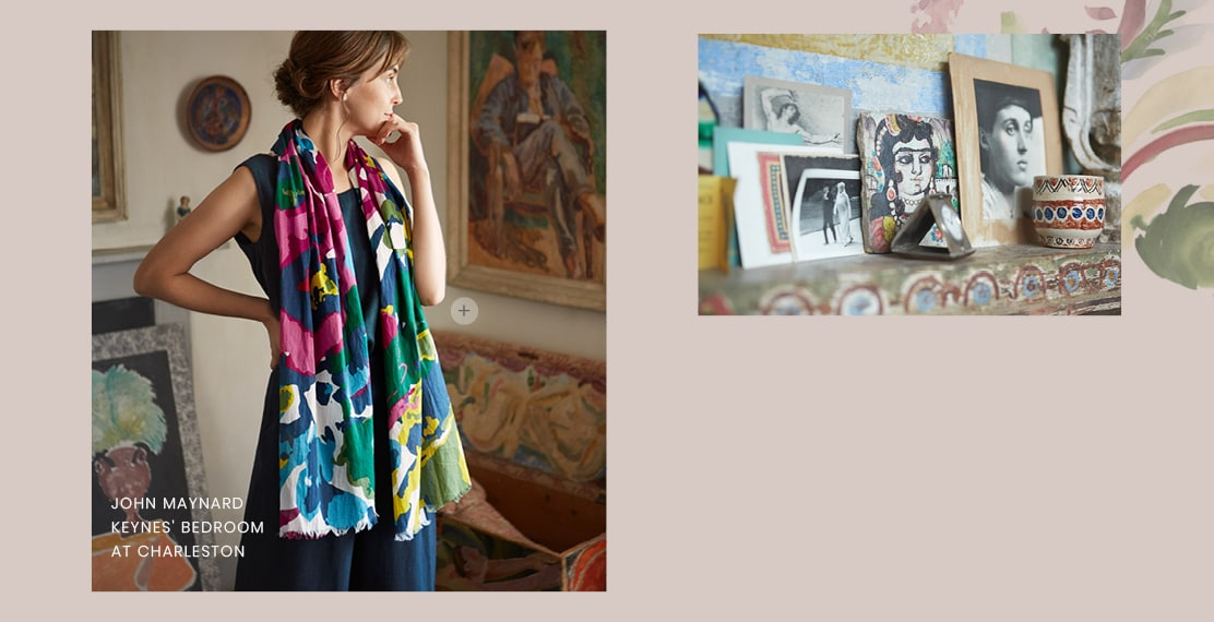 A women wearing a bright & colourful scarf with a navy tunic underneath. Lots of paintings hung in the room around her.